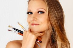 Beautiful woman holds make-up brush and puts on cosmetics on her face. Make up, cosmetics, beauty, eye lash extension stock images