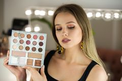 Beautiful woman holds makeup palette for eyes shadows in makeup studio with mirror stock photography