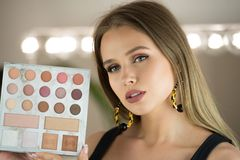Beautiful woman holds makeup palette for eyes shadows in makeup studio with mirror.  stock image