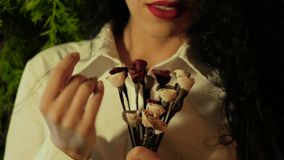 A beautiful woman holds out her hand with a bouquet and bring it to her face. Beautiful curly woman in white with a red lipstick on her lips holding a bouquet of stock video