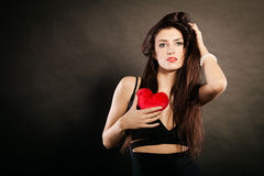 Beautiful woman holds red heart on black Stock Images
