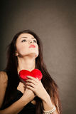 Beautiful woman holds red heart on black Royalty Free Stock Photos