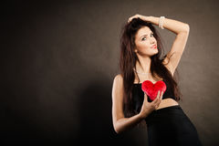 Beautiful woman holds red heart on black Royalty Free Stock Images