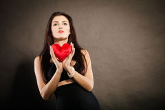 Beautiful woman holds red heart on black Stock Image