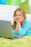 Beautiful woman at home laying floor with laptop. Beautiful woman at home laying at floor with laptop stock image
