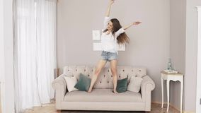 Beautiful woman at home listening music and dancing over the couch stock video