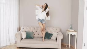 Beautiful woman at home listening music and dancing over the couch stock video footage