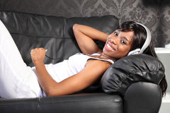 Beautiful woman at home lying down enjoying music Stock Photography