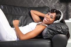 Beautiful woman at home lying down enjoying music Stock Photography