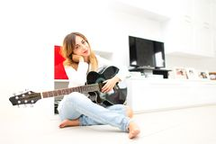 Beautiful woman in home sitting on the floor with her left-handed guitar Royalty Free Stock Photo