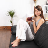 Beautiful woman at home on sofa drinking coffee Stock Photography