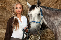 Beautiful Woman & Horse. Attractive, blonde, young woman holding the reins of a dapple gray horse surrounded by hay royalty free stock photos