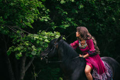 Beautiful woman on a horse. Dressed in long violet dress Stock Image