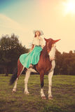 Beautiful woman with a horse in the field. Girl on a farm with a Royalty Free Stock Photos
