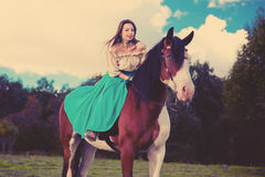 Beautiful woman with a horse in the field. Girl on a farm with a Stock Photos