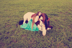 Beautiful woman with a horse in the field. Girl on a farm with a Royalty Free Stock Photo