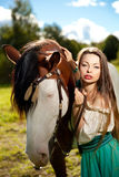 Beautiful woman with a horse in the field. Girl on Royalty Free Stock Photo
