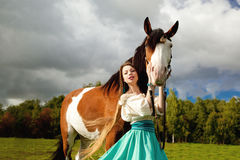 Beautiful woman with a horse in the field. Girl on Stock Photography