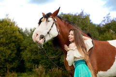 Beautiful woman with a horse in the field. Girl on Royalty Free Stock Image