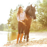 Beautiful woman and horse. On the river bank Royalty Free Stock Image