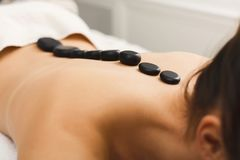 Woman getting hot stones massage at spa salon. Beautiful woman at hot stones massage in spa salon. Beauty treatment therapy, wellness and relaxation concept Stock Photos