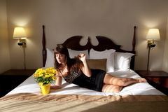 Beautiful Woman on Hotel Bed With Flowers Royalty Free Stock Image