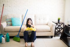 Woman using mobile phone after completing house chores. Beautiful woman housewife sitting on the floor and using phone Royalty Free Stock Photos