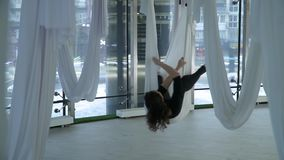 Beautiful woman hovers in yoga hammock, taking different poses in studio. Many white empty hammocks around. Modern. Beautiful woman hovers in hammock for yoga stock video footage