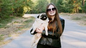 Beautiful woman hug caress funny pug dog in the park in slow motion. Holds on hands stock footage