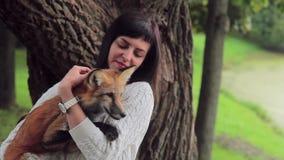Beautiful woman hug orange fox in park in weekend. stock footage