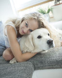 Beautiful woman hugging dog on sofa Stock Image