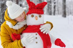 Beautiful woman hugging a snowman. Royalty Free Stock Image