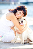 Beautiful woman hugs her dog. Beautiful young woman with her dog on a summer day sitting at the beach Royalty Free Stock Photos