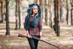 Beautiful woman hunter in forest with gun Stock Photos