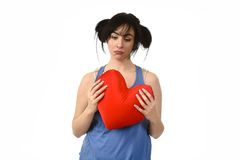 Beautiful woman hurt and suffering for lost love holding red heart shape pillow Stock Image