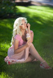 Beautiful woman with ice cream outdoors, girl eating icecrea in park, summer vacation. Pretty blond on nature. happy smiling woman Stock Photos