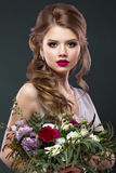 Beautiful woman in image of the bride with flowers. Beauty face and Hairstyle. Portrait of a beautiful woman in the image of the bride with flowers in her hands royalty free stock photography