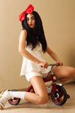 Beautiful woman in the image doll is sitting on small bicycle Royalty Free Stock Images