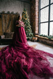 Beautiful woman in the image of the Queen in the Marsala-colored. Dress with a long train in the loft Royalty Free Stock Photo