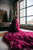 Beautiful woman in the image of the Queen in the Marsala-colored. Dress with a long train in the loft Royalty Free Stock Photography
