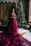 Beautiful woman in the image of the Queen in the Marsala-colored. Dress with a long train in the loft Stock Images