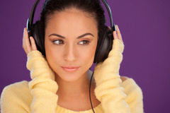 Beautiful woman immersed in her music. Listening intently to the tunes on a pair of stereo headphones Stock Photo