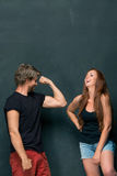 Beautiful woman impressed by the muscles of a bodybuilder, strong man showing off his muscles Royalty Free Stock Images