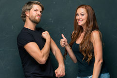 Beautiful woman impressed by the muscles of a bodybuilder, strong man showing off his muscles Stock Photos
