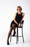 Beautiful Woman In Black Dress Posing Sitting On A Chair Stock Image