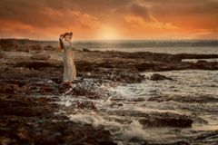 Beautiful Woman  In Rocks Seashore At Sunrise Royalty Free Stock Images