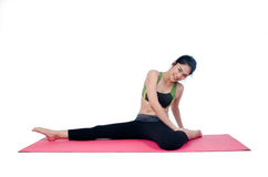 Beautiful woman indoor exercising using pink yoga mat Stock Image