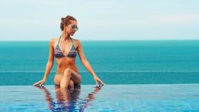 Beautiful woman in an infinity pool. With beautiful view stock photo