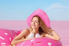 Beautiful woman with inflatable ring near lake stock image