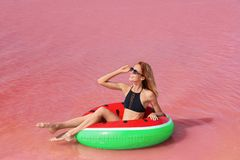 Beautiful woman on inflatable ring in lake stock photo